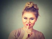 Mulher nova bonita com o dedo nos bordos Imagem de Stock