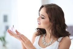 Mulher nova bonita com o frasco do perfume imagens de stock