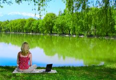 Mulher nova bonita com o portátil perto do lago foto de stock royalty free