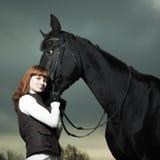 Mulher nova bonita com um cavalo preto Imagens de Stock
