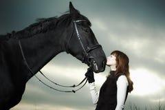 Mulher nova bonita com um cavalo preto Imagens de Stock Royalty Free
