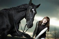 Mulher nova bonita com um cavalo preto Imagem de Stock