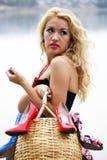 Mulher nova bonita com uma cesta cheia das sapatas Fotografia de Stock