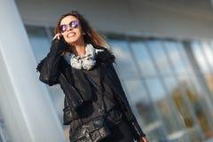 Mulher nova bonita da forma com a janela próxima da loja dos sacos de compras que chama o telefone esperto, tonificado Imagens de Stock