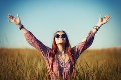 Mulher nova bonita da hippie que senta-se em um campo e que reza ao deus fotografia de stock royalty free