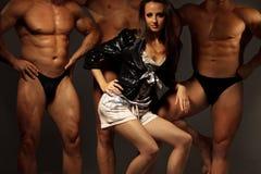 Mulher nova bonita de encontro a três atletas imagens de stock