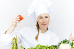 A mulher nova bonita do cozinheiro chefe prepara-se e decorando o alimento saboroso dentro Foto de Stock Royalty Free