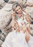 Mulher nova bonita do estilo do boho no vestido branco na praia de pedra Imagem de Stock Royalty Free