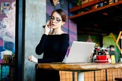 mulher nova bonita do freelancer na cafetaria Senhora bonita com o telefone esperto em suas mãos usando o portátil fotos de stock royalty free