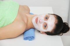 Mulher nova bonita dos olhos azuis com máscara do facial da argila fotografia de stock royalty free
