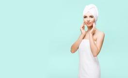 Mulher nova, bonita e natural envolvida na toalha sobre vagabundos cianos Fotos de Stock