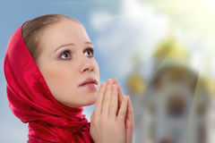 A mulher nova bonita em um lenço prays ao deus imagens de stock