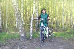 Mulher nova bonita Em uma bicicleta, estando nas madeiras contra o contexto de um bosque do vidoeiro fotos de stock royalty free