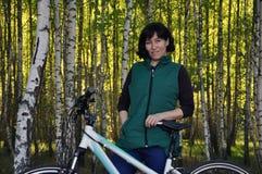 Mulher nova bonita Em uma bicicleta, estando nas madeiras contra o contexto de um bosque do vidoeiro imagens de stock