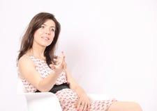 Mulher nova bonita em uma cadeira branca Fotografia de Stock Royalty Free