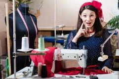 Mulher nova bonita engraçada do pinup com a máquina de costura que olha a câmera surpreendida Imagem de Stock