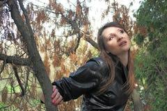 A mulher nova bonita escuta sons de uma madeira Fotografia de Stock Royalty Free
