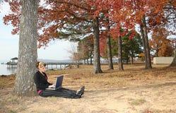 Mulher nova bonita no parque com portátil imagens de stock royalty free