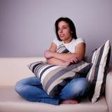 Mulher nova bonita, no sofá prestando atenção à tevê, Imagens de Stock