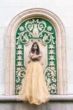 Mulher nova bonita no vestido do ouro Fotografia de Stock