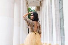 Mulher nova bonita no vestido do ouro Imagem de Stock Royalty Free
