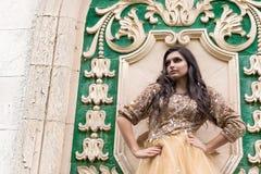 Mulher nova bonita no vestido do ouro Foto de Stock Royalty Free
