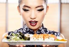 Mulher nova bonita que come o sushi Imagens de Stock