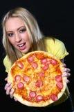 Mulher nova bonita que come a pizza fotografia de stock