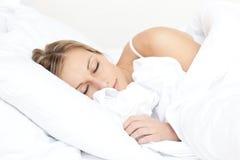 Mulher nova bonita que dorme em sua cama Fotografia de Stock Royalty Free