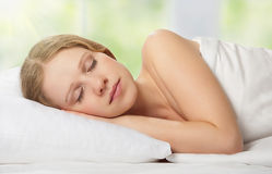 Mulher nova bonita que dorme na cama Fotografia de Stock
