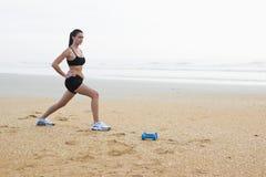 Mulher nova bonita que exercita na praia Fotos de Stock Royalty Free