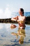 Mulher nova bonita que faz a ioga no mar Fotografia de Stock Royalty Free