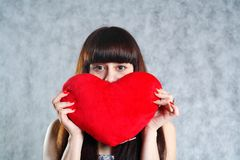 Mulher nova bonita que prende o coração vermelho Imagens de Stock Royalty Free