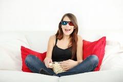 Mulher nova bonita que presta atenção à tevê nos vidros 3d Fotografia de Stock Royalty Free