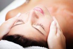 Mulher nova bonita que recebe a massagem facial. Imagem de Stock
