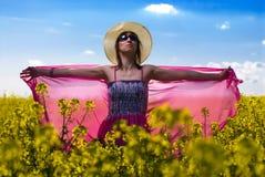 Mulher nova bonita que relaxa em um campo da couve-nabiça Imagens de Stock Royalty Free