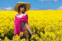 Mulher nova bonita que relaxa em um campo da couve-nabiça Foto de Stock