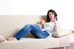 Mulher nova bonita que relaxa no sofá fotografia de stock royalty free