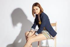 Mulher nova bonita que senta-se em uma cadeira Imagem de Stock