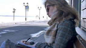 Mulher nova, bonita, bonita que senta-se no banco no parque, nas mãos de seu caderno Está vestindo um revestimento Faz vídeos de arquivo