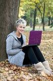 Mulher nova bonita que usa o portátil em ao ar livre Fotografia de Stock