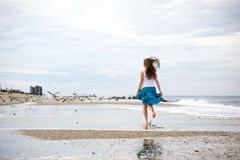 A mulher nova bonita tem o divertimento na costa do oceano Fotos de Stock Royalty Free