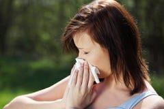 A mulher nova com alergia está limpando seu nariz. Fotografia de Stock