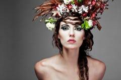 Mulher nova com as flores coloridas no cabelo. Fotos de Stock Royalty Free