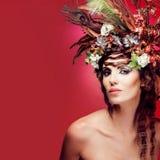 Mulher nova com as flores coloridas no cabelo. Fotografia de Stock Royalty Free