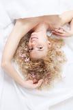 Mulher nova com as flores no cabelo na cama branca Fotografia de Stock Royalty Free