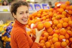Mulher nova com as laranjas na loja fotografia de stock