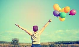 Mulher nova com balões coloridos Fotografia de Stock