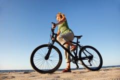 Mulher nova com bicicleta fotos de stock