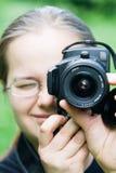 Mulher nova com câmera de DSLR foto de stock